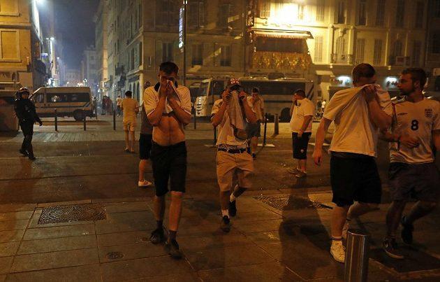 Angličtí fanoušci si utírají obličej poté, co dostali spršku od slzného plynu.