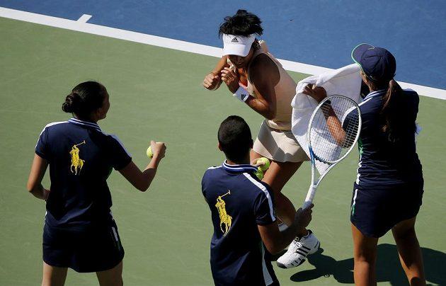 Podavači míčků s ručníky pomáhají Japonce Kimiko Dateové-Krummové čelit náletům bodavého hmyzu.