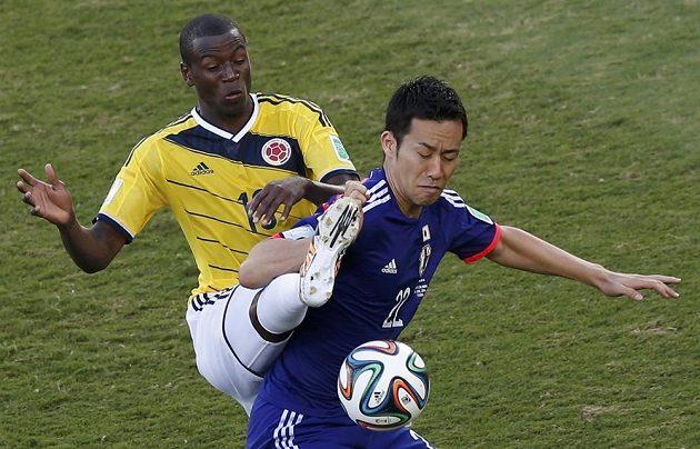 Kolumbijec Adrian Ramos (vlevo) bojuje o míč s Majem Jošidou z Japonska.