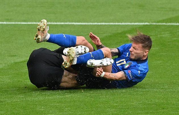 Rakouský brankář Daniel Bachmann leží na trávníku po střetu s Italem Cirem Immobilem v osmifinále EURO.