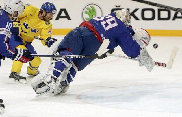 Švédský hokejista Jacob Josefson (druhý zleva) překonává francouzského gólmana Cristobala Hueta v utkání na MS v Praze.