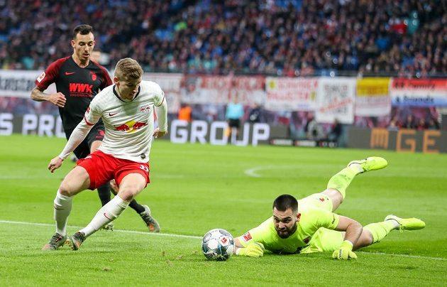 Český brankář Augsburgu se snaží zabránit ve skórování Timo Wernerovi z Lipska během bundesligového utkání.