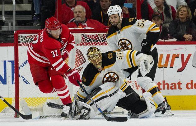 Útočník Caroliny Kris Versteeg (32) se snaží procedit puk za záda gólmana Bostonu Tuukky Raska (40) v zápase NHL. Raskovi kryje záda bek Adam McQuaid (54).