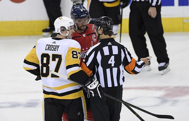 Hvězdy v akci. Lídr Pittsburghu Penguins Sidney Crosby (87) a ruský útočník Washingtonu Capitals diskutují s rozhodčím během utkání NHL.