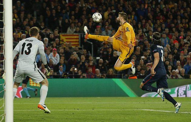Barcelonský Gerard Piqué (uprostřed) v akci před brankou Atlétika.