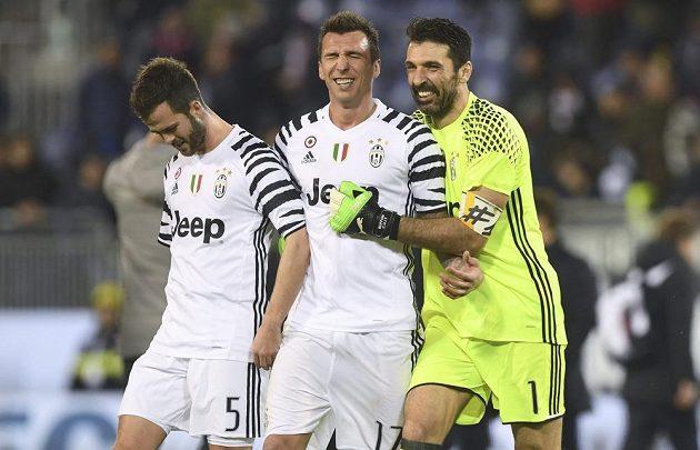 Fotbalisté Juventusu Turín se radují, vyhráli zápas italské ligy na půdě Cagliari 2:0. Na snímku slaví Gianluigi Buffon, Mario Mandžukič a Miralem Pjanič.