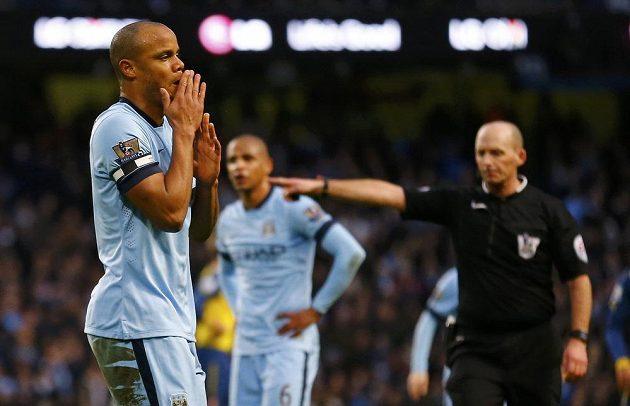 Kapitán Manchesteru City Vincent Kompany se drží za hlavu krátce poté, co sudí Mike Dean odpískal jeho faul a Arsenal následně proměnil pokutový kop.