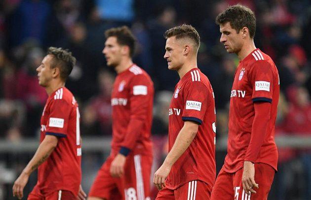 Fotbalisté Bayernu Thomas Müller se spoluhráči zklamaně odchází ze hřiště po domácí remíze s Freiburgem.