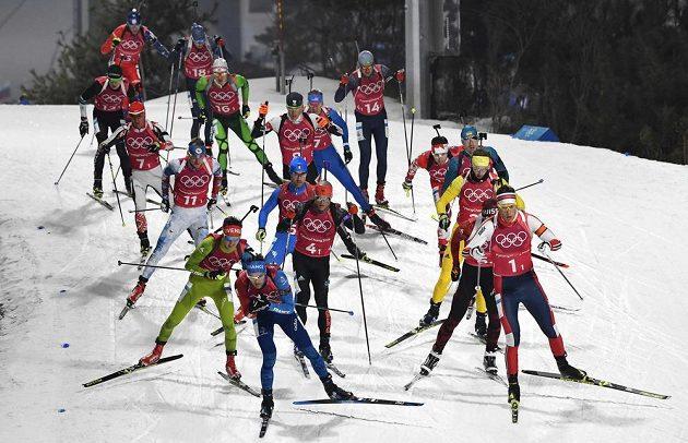 Balík biatlonistů při prvním úseku mužské štafety. Český reprezentant Ondřej Moravec (třetí zleva) jel s číslem 11.