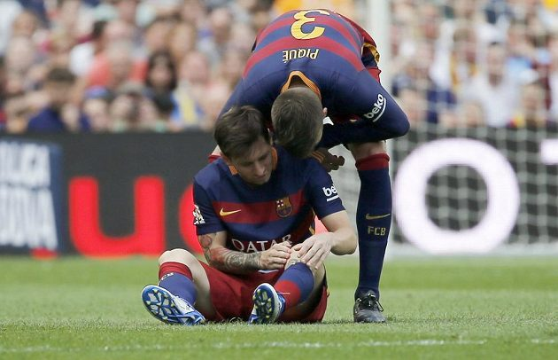 Spoluhráč Gerard Piqué se sklání nad zraněným Lionelem Messim.