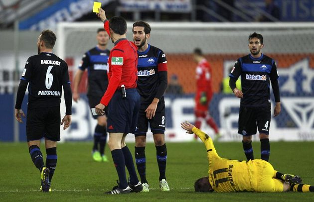 Rozhodčí Wolfgang Stark (v červeném) uděluje žlutou kartu paderbornskému Marvinu Bakalorzovi, na zemi zraněný dortmundský Marco Reus.