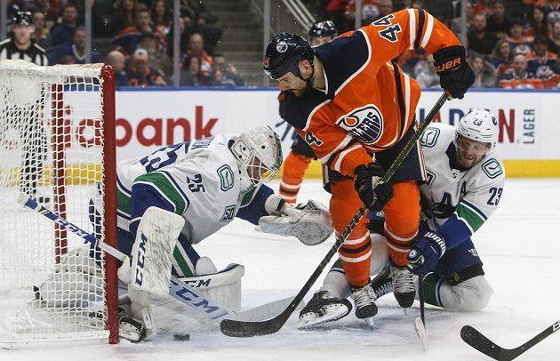 Gólman Vancouveru Markstrom (vlevo) při zákroku proti dorážce Kassiana z Edmontonu.