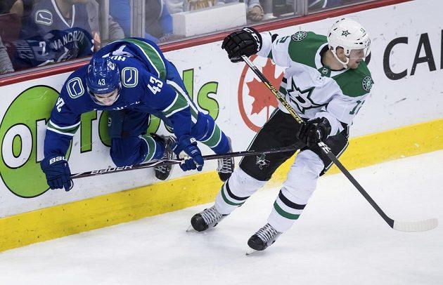 Český útočník Dallasu Radek Faksa ( v bílém) odjíždí ze souboje s Quinnem Hughesem během druhé třetiny zápasu NHL na ledě Vancouveru.