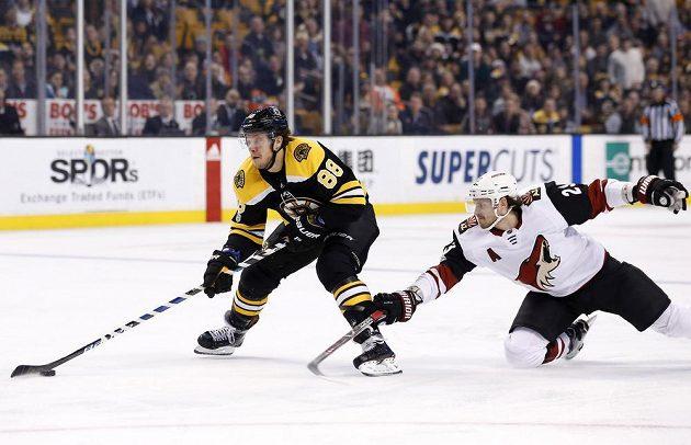 Obránce Arizony Coyotes Oliver Ekman-Larsson se snaží zastavit unikajícího Davida Pastrňáka z Bostonu v utkání NHL.