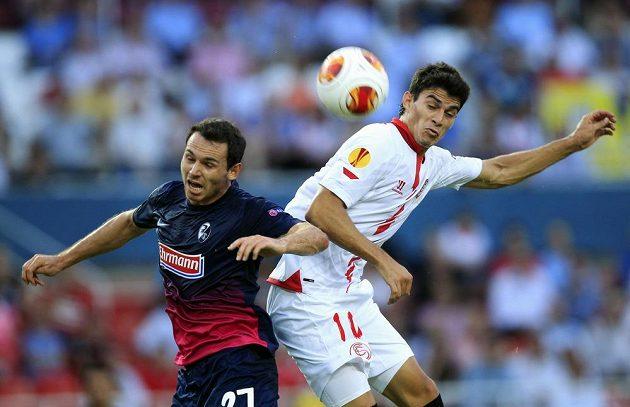 Diego Perotti ze Sevilly (vpravo) v hlavičkovém souboji s Nicolasem Hoflerem z Freiburgu.