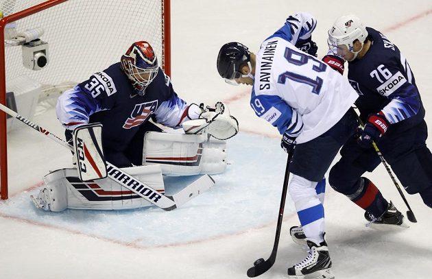 Finský útočník Veli-Matti Savinainen před americkým brankářem Corym Schneiderem, brání ho Brady Skjei (vpravo).