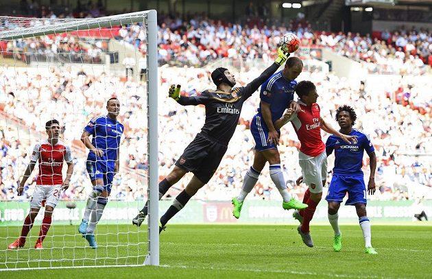 Gólman Arsenalu Petr Čech vyráží míč před naskakujícím obráncem Chelsea Branislavem Ivanovičem.