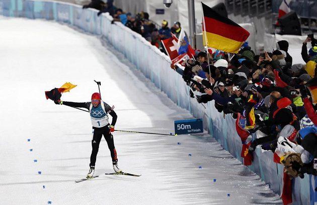 Německá biatlonistka Laura Dahlmeierová finišuje s německou vlajkou pro své druhé individuální zlato v Pchjongčchangu.