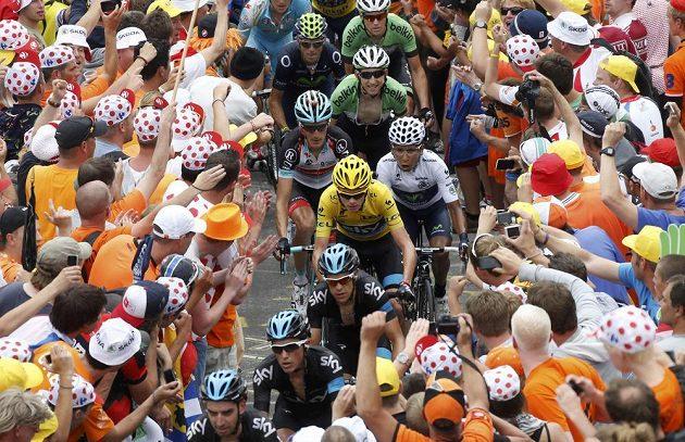 Cyklisté obklopení fanoušky během náročného stoupání.