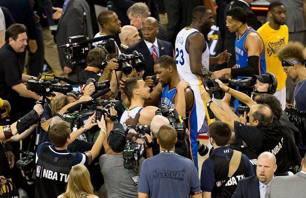 Stephen Curry z Golden State (uprostřed v bílém dresu) Kevin Durant z Oklahomy se zdraví po sedmém finále play off Západní konference NBA.