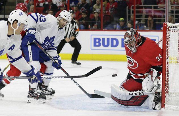 Hokejisté Toronta Maple Leafs Patrick Marleau a Nazem Kadri se snaží vyzrát na Petra Mrázka v brance Caroliny v utkání NHL.