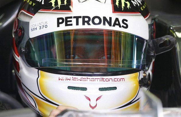 Lewis Hamilton pozoruje dění v boxech při měřeném tréninku na okruhu v Sepangu.