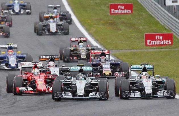 Nico Rosberg se svým mercedesem předjíždí v úvodní zatáčce GP Rakkouska svého týmového kolegu Lewise Hamiltona (vpravo).