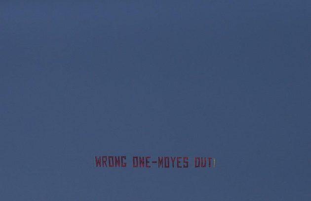 """Letadlo s transparentem """"Ten nesprávný - Moyes ven"""" se varovně v rámci akce fanoušků vznášelo nad stadiónem Old Trafford."""