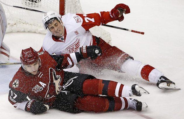 Parvé křídlo Arizony Coyotes Radim Vrbata (17) padá při souboji s Dylanem Larkinem z Detroitu Red Wings během utkání NHL.