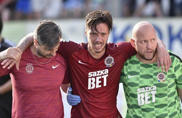 Lékař Sparty Miroslav Sinkule (vlevo) a masér Kamil Maixner (vpravo) pomáhají zraněnému útočníkovi Sparty Václavu Kadlecovi.
