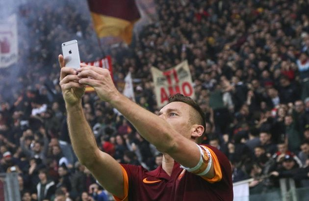 Kapitán AS Řím Francesco Totti si fotí skandující příznivce.