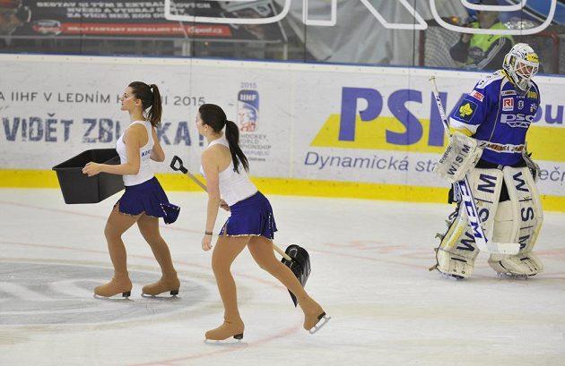 Zlínský brankář Tomáš Štůrala se koncentruje, zatimco dívky uklízejí ledovou plochu.