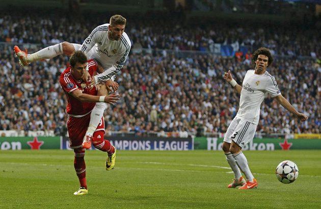 Mnichovský Mario Mandžukič (v červeném dresu) v souboji se Sergiem Ramosem, vpravo další hráč Realu Pepe.