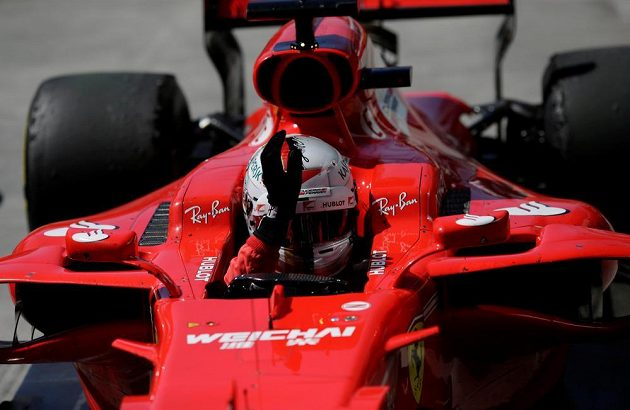 Pilot Ferrari Sebastian Vettel zdraví fanoušky po triumfu v Brazílii.