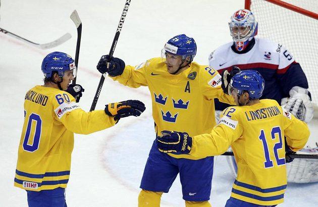 Švédští hokejisté slaví gól proti Slovensku. Zleva střelec branky Mikael Backlund, Jimmie Ericsson a Joakim Lindström. Vzadu je smutný brankář Ján Laco.