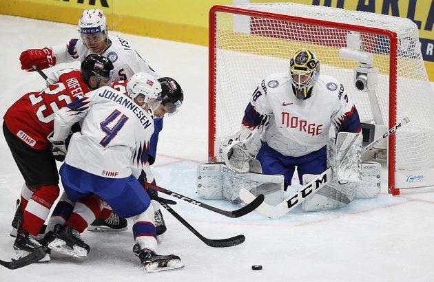 Norský brankář Henrik Holm a jeho parťáci Johannes Johannesen a Erlend Lesund se snaží zabránit ve skórování rakouskému hokejistovi Fabiu Hoferovi v utkání mistrovství světa.