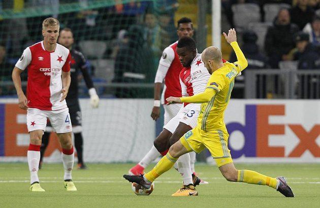 Fotbalista Slavie Michael Ngadeu-Ngadjui v souboji s Ivanem Majevským z Astany v utkání Evropské ligy.