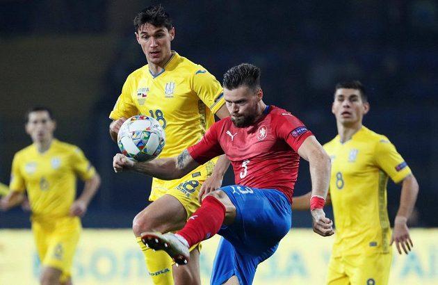 Ondřej Čelůstka odkopává míč před Ukrajincem Romanem Jaremčukem.