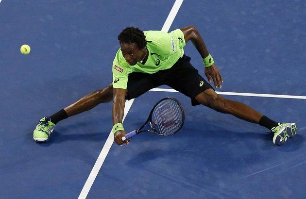 Gael Monfils z Francie v krkolomné pozici sleduje míček v zápase s Rogerem Federerem ze Švýcarska.