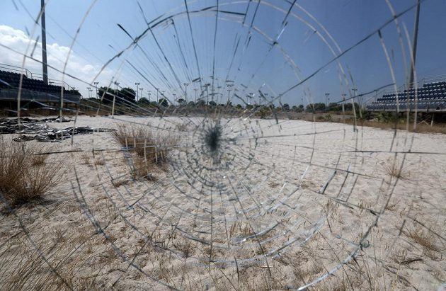 Odraz zpustošeného beachvolejbalového stadiónu v Aténách v rozbitém skle.