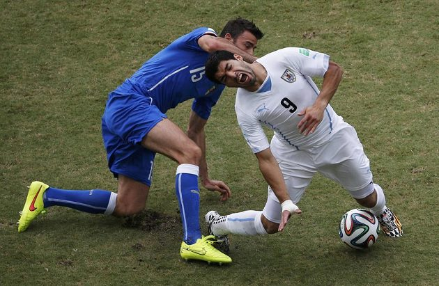 Uruguayský snajpr Luis Suárez (vpravo) padá po zákroku Itala Andrey Barzagliho.
