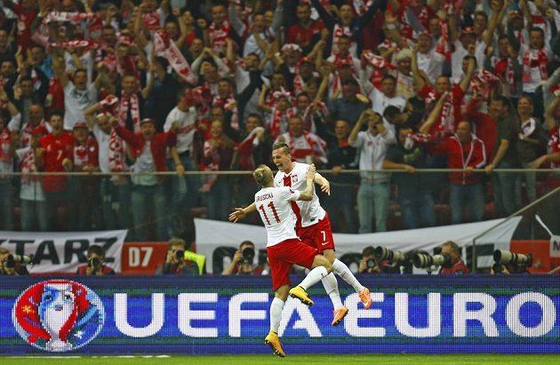 Polský útočník Arkadiusz Milik (vpravo) oslavuje se spoluhráčen Kamilem Grosickim svůj gól proti Německu.