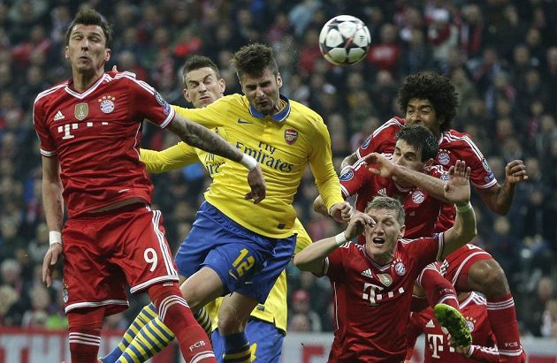 Fotbalista Arsenalu Oliver Giroud (uprostřed) hlavičkuje v obležení hráčů Bayernu Mnichov v odvetě osmifinále Ligy mistrů.