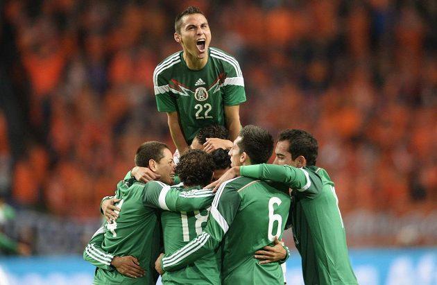 Mexický obránce Paul Aguilar (nahoře) slaví se svými spoluhráči vedoucí gól útočníka Carlose Vely v Amsterdamu nad domácím Nizozemskem.
