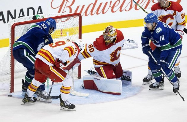 Český gólman Calgary Flames Daniel Vladař sleduje, kde skončí puk po závaru před jeho brankou v přípravném duelu s Vancouverem Canucks.