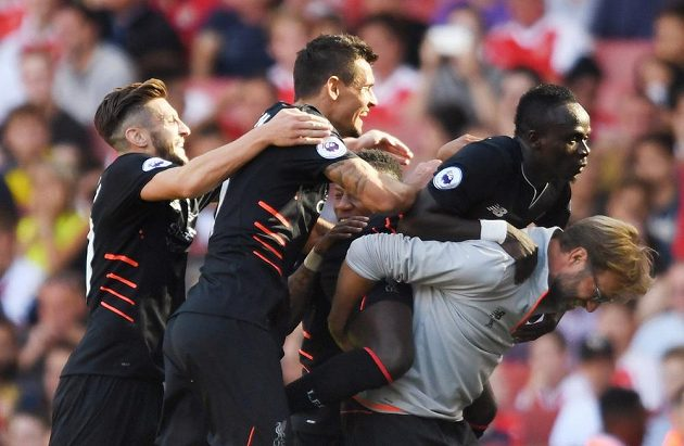 Liverpoolští fotbalisté oslavují s koučem Jürgenem Kloppem gól proti Arsenalu.