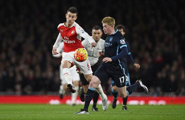 Laurent Koscielny (vlevo) z Arsenalu odkopává míč před Kevinem De Bruynem z Manchesteru City.