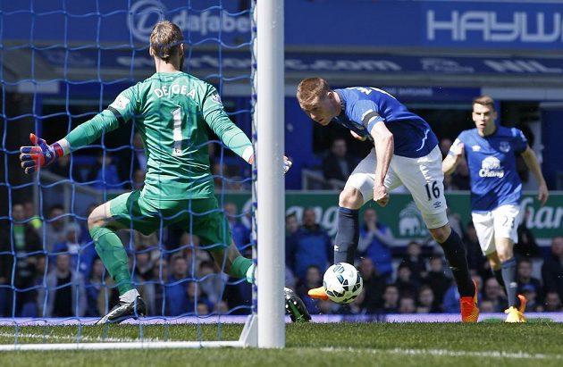 Záložník Evertonu James McCarthy (uprostřed) překonává brankáře Manchesteru United De Geu v utkání 34. kola Premier League.