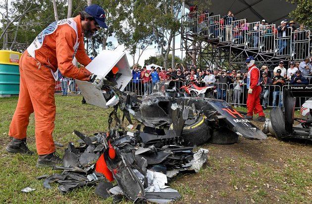 Jeden z pořadatelů hází na jednu hromadu kusy z Alonsova monopostu při Velké ceně Austrálie.