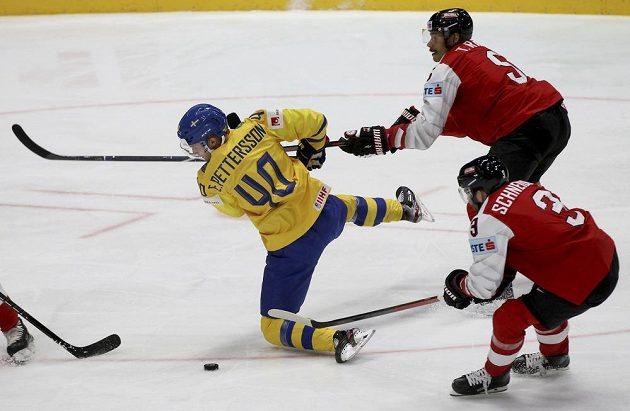 Švédský hokejista Elias Pettersson padá po ataku Rakušana Thomase Raffla v utkání mistrovství světa. Vše sleduje další Rakušan Peter Schneider.